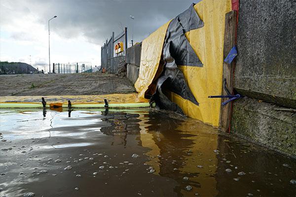 Гибкая плотина Water-Gate ©, прислоненная к стене. Передняя кромка закреплена доской для уменьшения протечек при заливке воды.