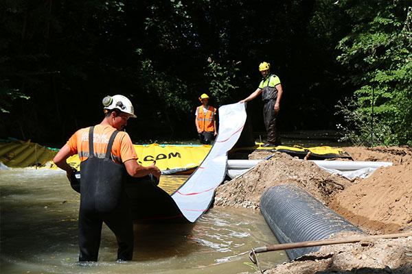 Гибкий сливной шланг DP-3075 диаметром 450 мм присоединяется к водосливу Water-Gate ©. Затем мы полностью выкатываем вниз по течению перед заливкой воды.