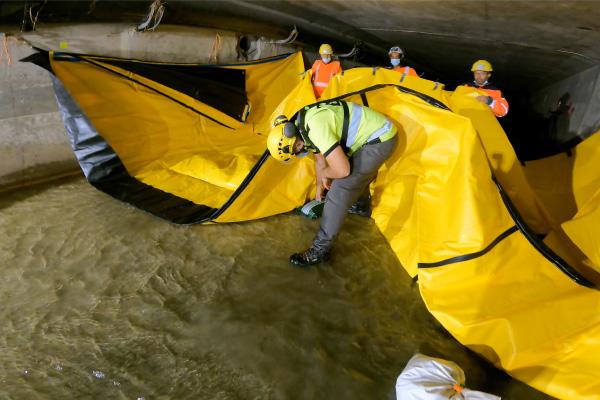 Поместите мешки с гравием на землю под гибкой плотиной Water-Gate © для увеличения сил трения.